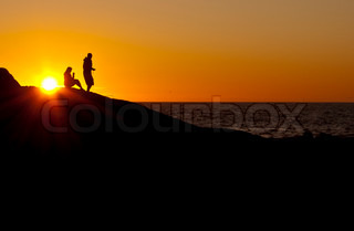 silhouettes of two people at sunset