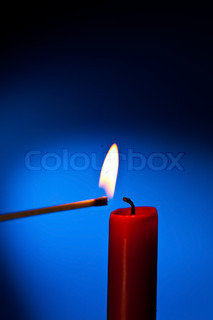 a red candle is lit with a match
