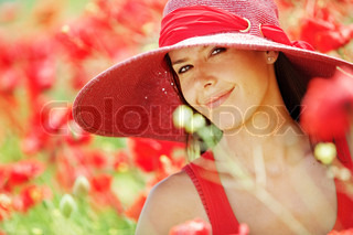 Portrait of young beautiful woman at poppy field