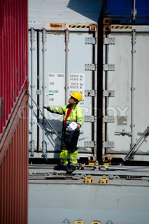 Man directing crane loading a container ship