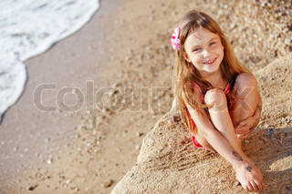 Cute child wearing swimsuit resting at beach in summer