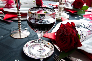Festive table setting for Christmas with silver and red rose