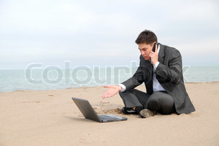 A young businessman sitting c in front of a laptop and talking on a mobile phone
