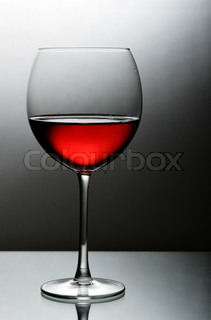 Glass of red wine close-up over black and white background