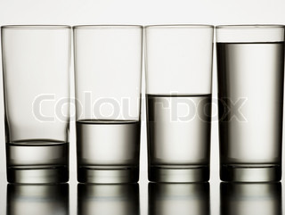 Close-up of four glasses of water in a row