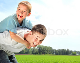happy brothers playing in the summer field