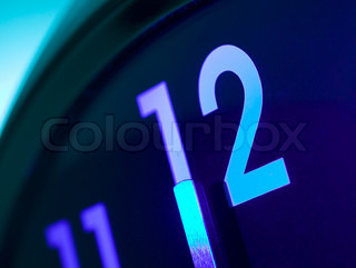 Top area of a wall clock showing 12 am pm