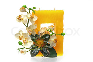 Large yellow candle with the flower decoration isolated on white background