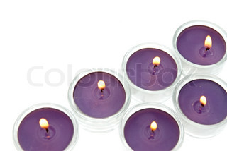Purple candles in glass isolated on white background