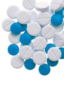 Macro view of white and blue pills on blue background