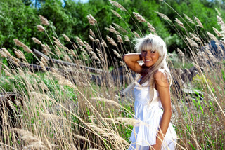 girl in white dress are standing in dry grass at summer daylight