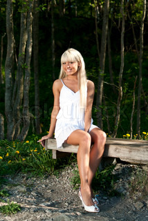 Girl in white dress sitting on a bench in the woods