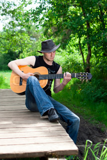 Man Playing Guitar In The Woods On The Bridge Stock