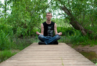 man sitting in the lotus position and meditates on the bridge in the forest