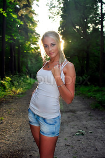 girl in jeans posing in the woods at sunset