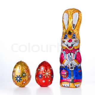 wrapped chocolate easter bunny with eggs isolated