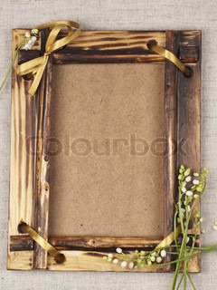 Old wooden frame for a picture with the lilies of the valley