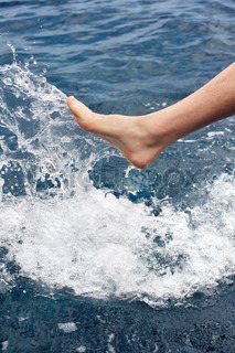 Foot of young man in water - splash