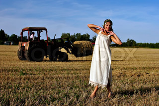 girl in a rural clothing standing on the field, tractor on the background