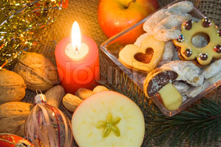 Christmas atmosphere - candle, apple, sweets and Christmas decorations