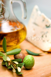 bottle of olive oil on old wooden table and an olive branch