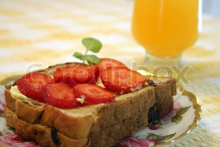Toast topped with tasty strawberries and glass of orange juice