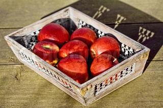 Red apples in a basket with wood texture background