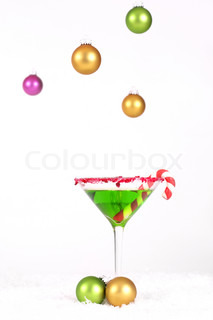 Christmas Drink and hanging coloured baubles decoration on a winter snow white background
