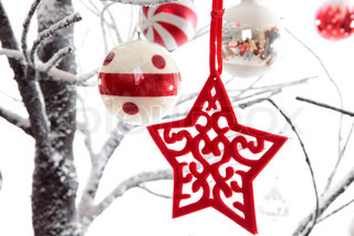 Christmas decorations dangling from snow covered branches
