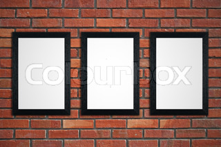 Three black picture frames on red brick wall