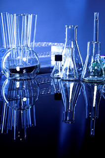 Laboratory glassware on navy-blue background with reflex on table