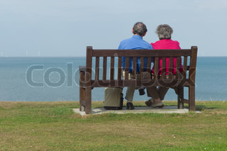 An elderly couple relax on a seat at the sea