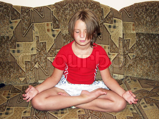 The girl in the lotus position on the couch