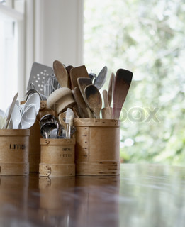 Kitchen utensils in containers on table in the kitchen