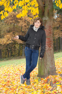 En ung pige i besiddelse af en telefon under træet farve under cherry farvede nedfaldne blade
