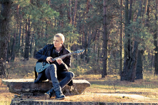 teen musician plays the guitar in the autumn forest