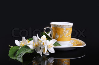yellow cup on black with jasmine flower