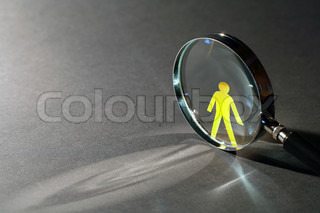 Yellow paper man near magnifying glass on dark background with beam of light