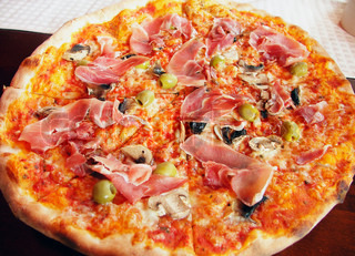 Italian pizza with italian ham, olives and field agaric.