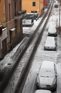 City street covered by first snow in Alba, Italy