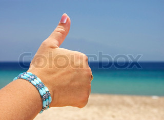 Thumbs up hand sign isolated on exotic background
