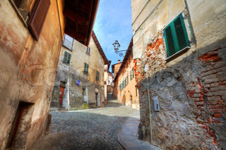 Narrow paved street among old historic houses in Saluzzo, northern Italy