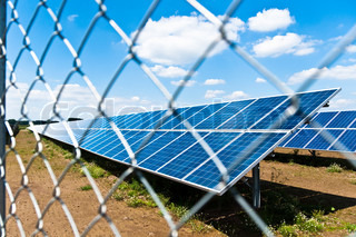 Large solar panels in photovoltaic park behind fence with great blue cloudy sky