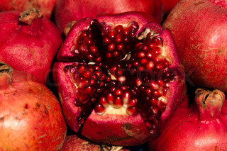 Closeup on several pomegranate fruits, the center one is cut in halves
