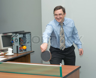 The man at office plays table tennis