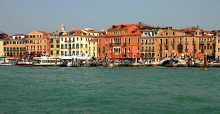 architecture of Venice, view from sea, boats and tourists by colorful buildings