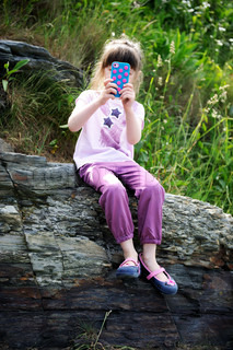 Little girl sitting on the rocks with mobile phone taking snapshots
