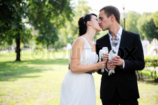Beautiful bride and groom kissing outdoors in the park