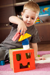 Little boy aged three is building a tower with toy blocks