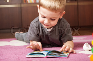 Cute boy aged 3 is lying on the flor and reading book